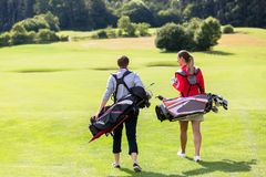 Rear view of golfing couple walking on golf green. Rear view of golfing couple carrying golf kit walking on golf green royalty free stock images