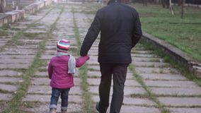 Rear view of granddaughter and grandfather walking in the city park holding hands.