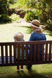 Rear view of granddaughter and grandmother wearing hats sitting on wooden bench Royalty Free Stock Photos