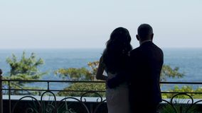 Rear view the groom hugs the bride and they look at the sea from the balcony stock video footage