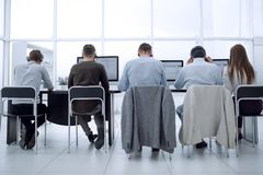 Rear view.a group of call center employees sitting at the Desk. royalty free stock images