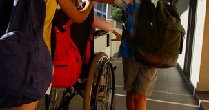 Schoolkids pushing disabled schoolgirl in wheelchair at corridor 4k. Rear view of group of diverse schoolkids pushing disabled Caucasian schoolgirl in wheelchair stock video