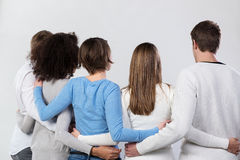 Rear view of a group of friends arm in arm Stock Photos