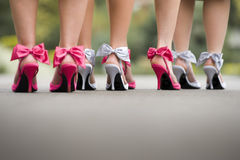 Rear view of a group ladies wearing colourful bow high heels. Low angle rear view of a group ladies wearing colourful bow high heels on road, or sidewalk Stock Photo