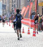 Rear view of a group of runners in an cobblestone alley Royalty Free Stock Images