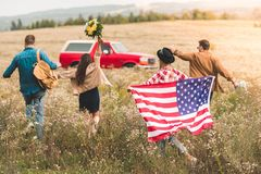 Rear view of group of young american travellers with flag walking by flower field during. Car trip royalty free stock image