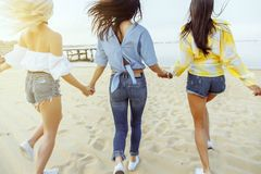 Rear view. A group of young attractive women holding hands running towards the water royalty free stock photography