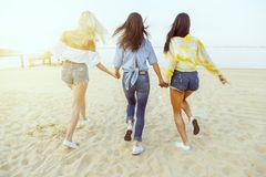 Rear view. A group of young attractive women holding hands running towards the water.  stock images