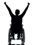 Rear view handicapped man arms raised  in wheelchair silhouette. One handicapped man arms raised  rear view in silhouette studio  on white background Stock Image