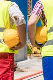 Rear view of the hands of two workers holding yellow hard hats Royalty Free Stock Photography