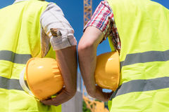 Rear view of hands of workers holding yellow hard hats of contruction workers Stock Image