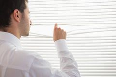 Rear view of handsome businessman spying through roller blind Royalty Free Stock Photos