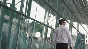 Rear view of handsome businessman with suitcase in modern airport terminal glass wall background. Travelling guy concept.  stock video footage