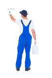 Rear view of handyman using paint roller on white background Stock Photos