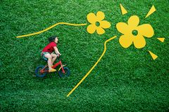 Rear View of a Happy Asian Kids. Girl on Bicycle Lay Down at Green lawn in Spring or Summer Day. Excited Asian Children in her Outdoor Activity stock photo