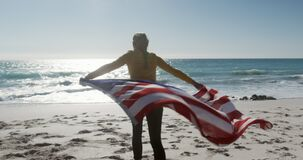 Woman holding American flag on the beach