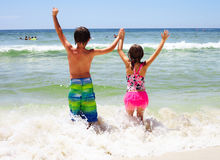 Rear view of happy children holding arms in water Royalty Free Stock Photos