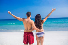 Rear view of happy couple with arms outstretched at the beach Royalty Free Stock Image
