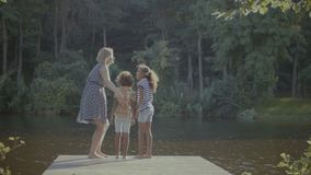 Diverse family standing on wooden jetty by lake. Rear view of happy diverse family with two cute preteen mixed race daughters standing barefoot on wooden jetty stock video footage