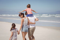 Rear view of happy family walking at beach Royalty Free Stock Image