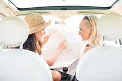 Rear view of happy female friends reading map in car Stock Image