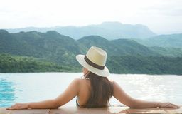 Rear view of happy lifestyle women relax and enjoy in the pool looking at mountain landscape.  Women together on summer and vacati Stock Images