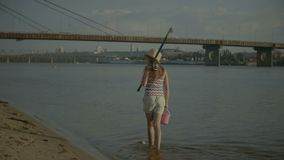 Happy little girl with fishing rod walking in water stock footage