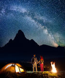 Rear view happy tourist family - man and woman holding hands, standing near tent and campfire Stock Image