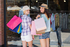 Rear view of happy women smiling at camera with shopping bags Stock Images
