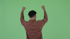 Rear view of happy young African man with fists raised. Studio shot of young handsome African man with dreadlocks against chroma key with green background stock footage