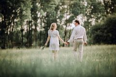Rear view. happy young couple walking on the lawn in the Park. The concept of family happiness stock image