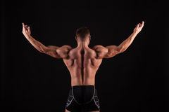 Rear view of healthy muscular young man with his arms stretched out isolated on black background Stock Images