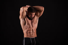 Rear view of healthy muscular young man with his arms stretched out isolated on black background Stock Photography