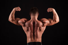 Rear view of healthy muscular young man with his arms stretched out isolated on black background Royalty Free Stock Images