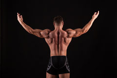 Rear view of healthy muscular young man with his arms stretched out isolated on black background Stock Photos