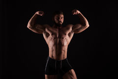 Rear view of healthy muscular young man with his arms stretched out isolated on black background Royalty Free Stock Photo