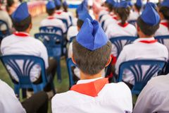 Rear view, high school students during class. Red scarf and blue beret are symbol of Lao People's Revolutionary Youth Union. royalty free stock photo