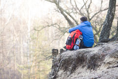 Rear view of hiker with backpack sitting on edge of cliff in forest Royalty Free Stock Photo