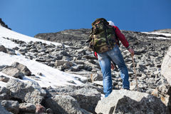 Rear view of hiker climbing on steep stony slope in mountains Royalty Free Stock Photography