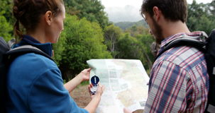 Rear view of hikers looking a map with a compass stock video footage