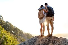 Rear view of hiking couple with backpack standing together on hill top enjoying beautiful landscape. Man and woman outdoors on. Rear view of hiking couple with royalty free stock photo