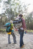 Rear view of hiking couple with backpacks walking in forest Royalty Free Stock Photos