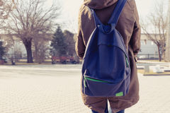 Rear view of hipster girl carring backpack on her back, copyspace Royalty Free Stock Image