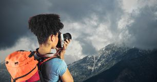 Rear view of hipster taking pictures of mountains against cloudy sky Royalty Free Stock Photo