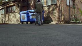 Rear view of homeless man pushing shopping cart to trash can. Tramp searching for food and empty bottles in trash can stock video footage