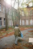 Rear view of homeless man pushing stolen shopping cart. Stock Image