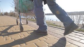 Rear view of homeless man`s legs walking with cart