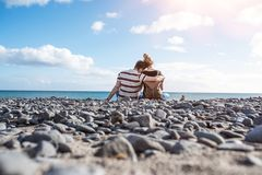 Rear view of hugging couple sitting on natural pebble beach. Against ocean and beautiful sky Royalty Free Stock Images