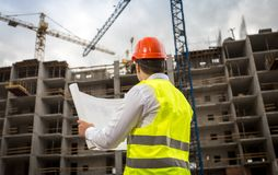 Rear view image of construction engineer looking at blueprints and working cranes on building site. Rear view photo of construction engineer looking at stock photo