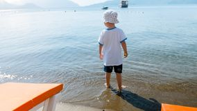 Rear view image of little toddler boy standing in the sea water and looking away royalty free stock images